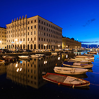 A view of the Gran Canale in Trieste, Italy with people enjoying the warm weather and boats moored in the water