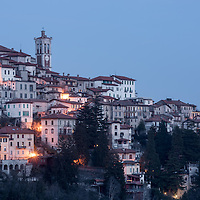 Panoramic view of the Ancient town of Santa Maria Del Monte near Varese, Italy at night with illuminated houses and the church bell tower (campanile)