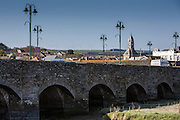 Fifteenth century bridge across the River Camel in Wadebridge, North Cornwall, United Kingdom.  A wind farm can be seen in the background. Wadebridge Renewable Energy Network (WREN) is a grass roots social enterprise aiming to transform the area into the first renewable energy powered town in the UK.