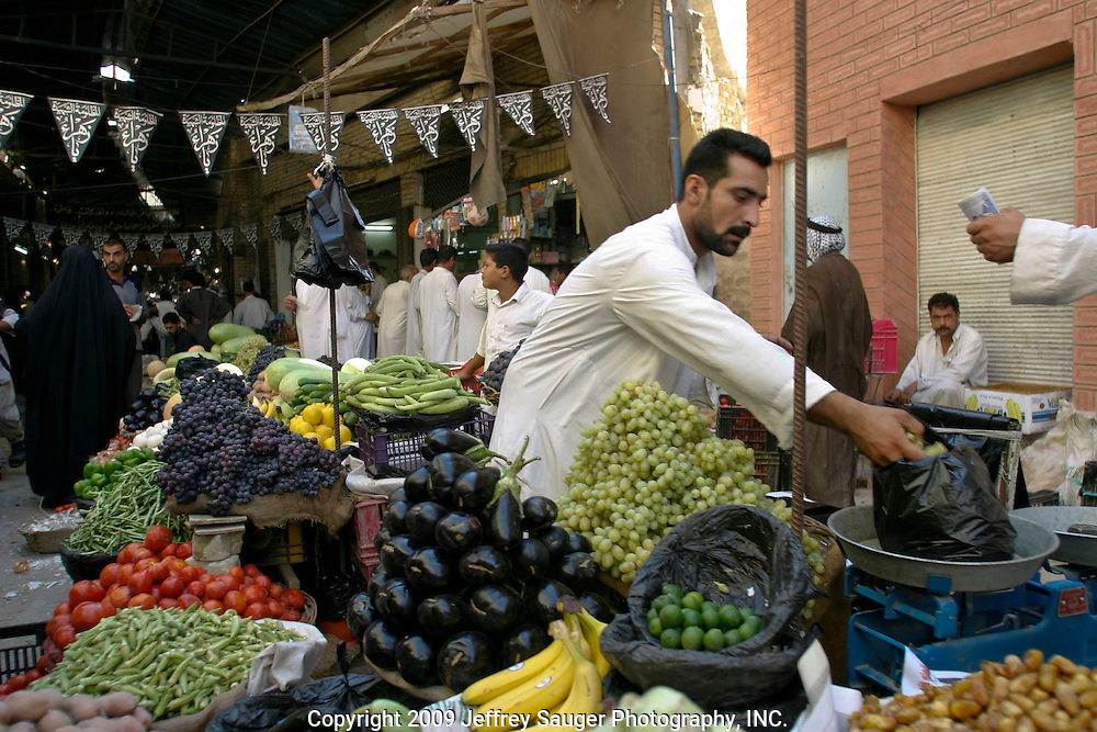 An Iraqi Shiite sells produce from his basteya, or produce stand in the market in Karbala, Iraq, Wednesday, July 23, 2003. Models of self-determination, Shiite controlled areas like Karbala are safer and starting to thrive more than under Saddam Hussein's regime. As the Shiite spiritual leader Ayottallah Ali Sistani has told his people to have patience with America, their patience is wearing thin with what they perceive as an occupation.