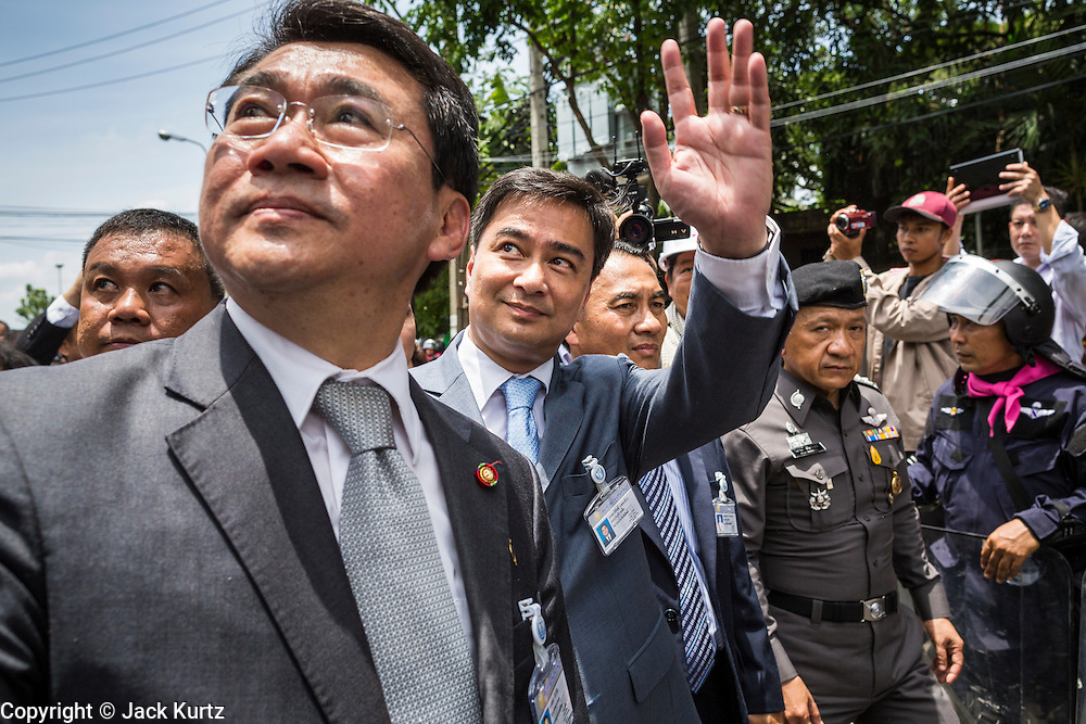 07 AUGUST 2013 - BANGKOK, THAILAND: Former Thai Prime Minister ABHISIT VEJJAJIVA, center, waves to supporters while he walks with members of his party to the Thai Parliament building during anti-amnesty protests in Bangkok. Abhisit's party, the Democrats, organized the anti-amnesty protest. About 2,500 protestors opposed to an amnesty bill proposed by Thailand's ruling party marched towards the Thai parliament in the morning. The amnesty could allow exiled fugitive former Prime Minister Thaksin Shinawatra to return to Thailand. Thaksin's supporters are in favor of the bill but Thai Yellow Shirts and government opponents are against the bill. Thai police deployed about more than 10,000 riot police and closed roads around the parliament. Although protest leaders called off the protest rather than confront police, a few people were arrested for assaulting police when they tried to break through police lines. Several police officers left the scene under medical care after they collapsed in the heat.    PHOTO BY JACK KURTZ