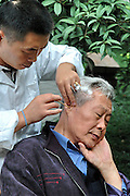 China, Local Chinese medicine, ear cleaning in a park
