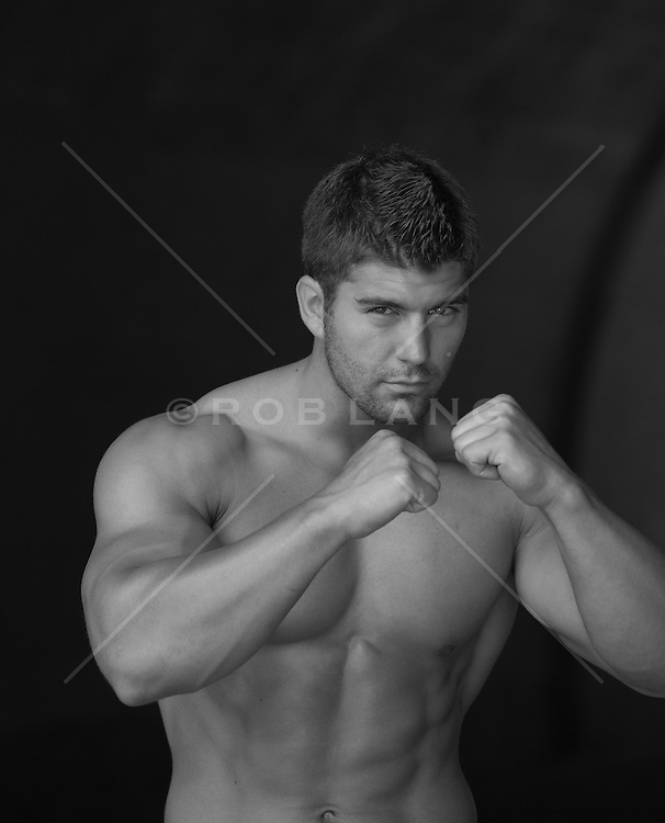 shirtless muscular boxer practicing his punches