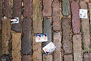 Op straat liggen een paar verloren pasfoto's