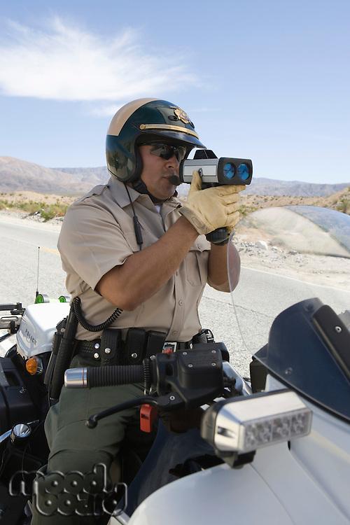 Police man using speed gun on road