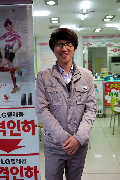 Store clerk selling mobile phones in the Daegu Metropolitan City which is the third largest metropolitan area in South Korea, and by city limits, the fourth largest city with over 2.5 million people. Daegu, South Korea, Republic of Korea, KOR, 22nd of April 2010.