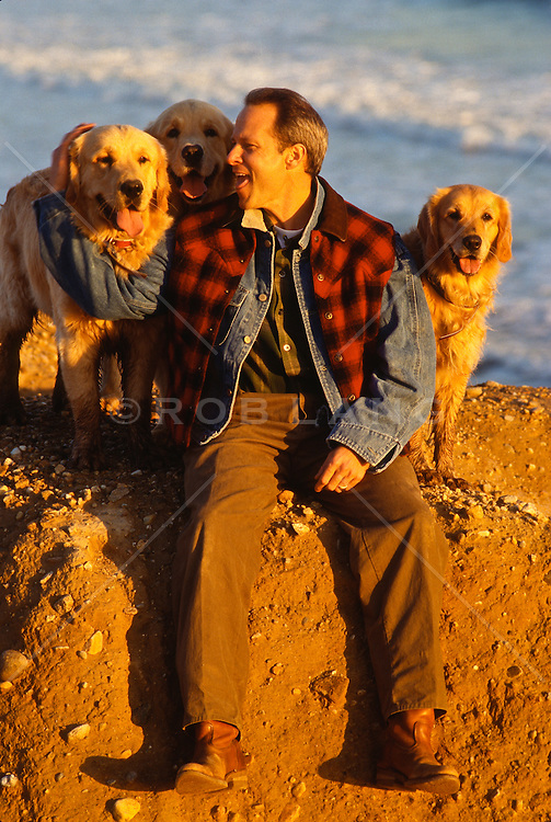 Man sitting on a cliff with Golden Retrievers In Montauk, NY