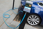 A blue Tesla Model S car recharges its batteries from a street recharging point provided by pay-to-use Polar Network from an Elektrobay charge point in St. James's Square, on 29th April 2019, in London, England.