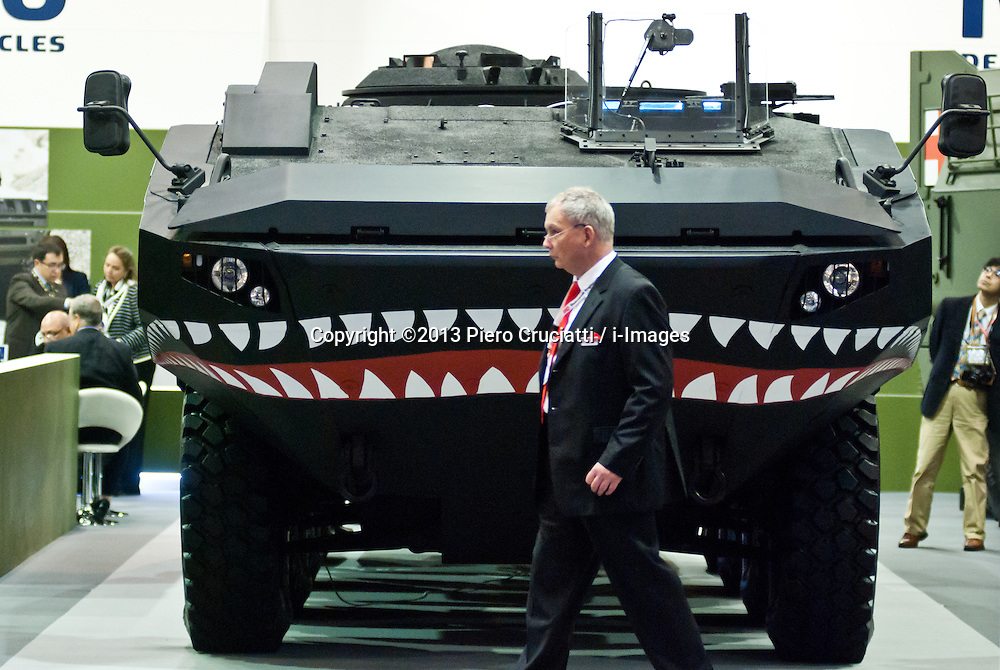 DSEI arms fair in London.<br /> A businessman walks past an Iveco vehicle during the 2013 edition of DSEI at Excel London, the World Leading Defence &amp; Security Event. London, United Kingdom. Tuesday, 10th September 2013. Picture by Piero Cruciatti / i-Images