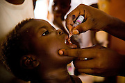 A health worker vaccinates a child during a national polio immunization exercise in Salaga, northern Ghana on Thursday March 26, 2009.