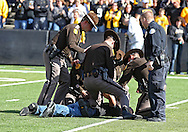 October 22, 2011: Iowa State Patrol officers tackle a fan who ran onto the field during the second half of the NCAA football game between the Indiana Hoosiers and the Iowa Hawkeyes at Kinnick Stadium in Iowa City, Iowa on Saturday, October 22, 2011. Iowa defeated Indiana 45-24.