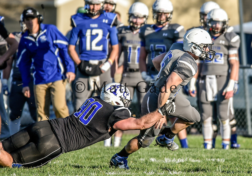 Dakota Wesleyan grey's Luke Loudenberg (16) slips out of the grip of Dakota Wesleyan black's Brady Mudder (90) during the spring game on Thursday night at the DWU practice field. (Matt Gade/Republic)