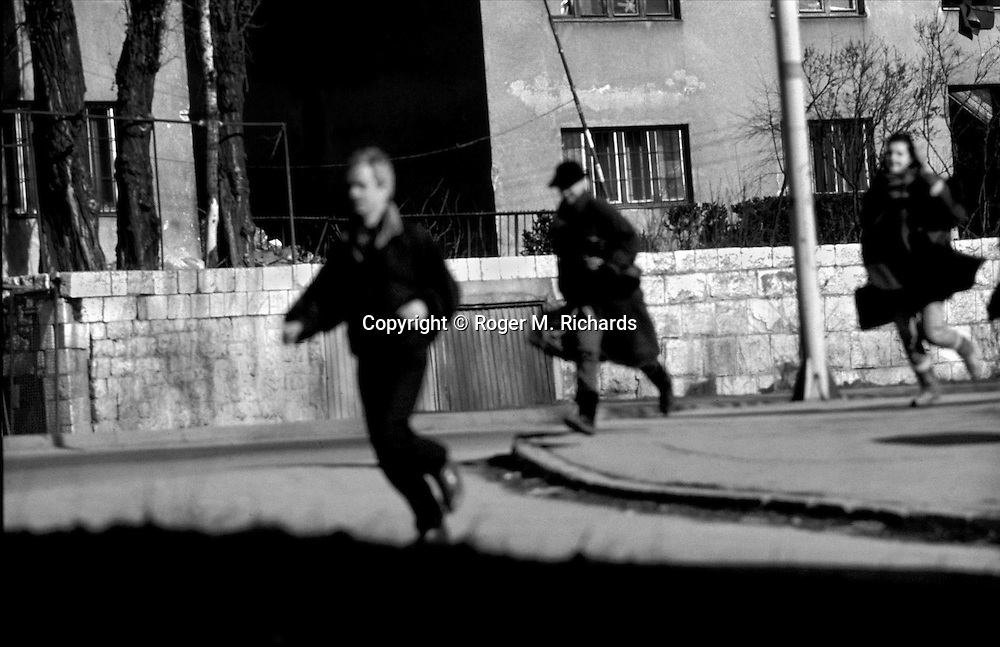 Sarajevo residents dash across an intersection under fire from a Serb sniper during the siege of the city, Sarajevo, Bosnia and Herzegovina, April 1993. PHOTO BY ROGER RICHARDS