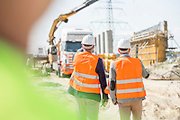Rear view of supervisors walking at construction site