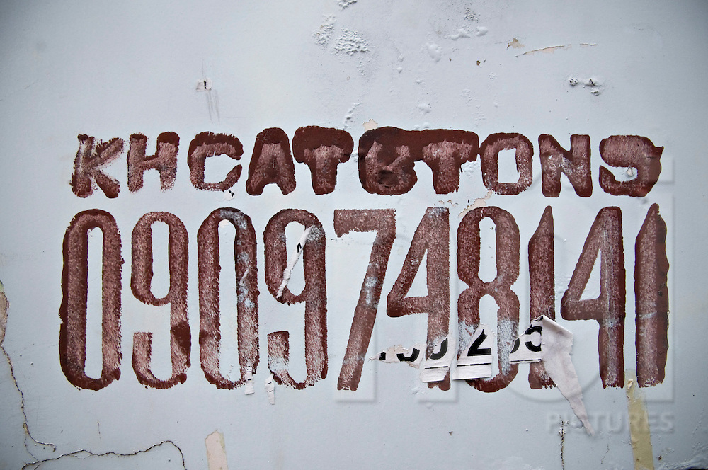 Painted phone numbers on a wall in Ho Chi Minh city (HCMC), Vietnam, Asia