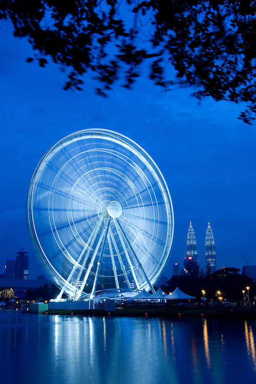 A 60-metre-high Ferris wheel stands against Petronas Towers as fireworks explode in the sky, Kuala Lumpur, Malaysia. Ferris whell called 'Eye on Malaysia' similar to the 'London Eye' will be one of the main attractions for the Visit Malaysia year 2007.