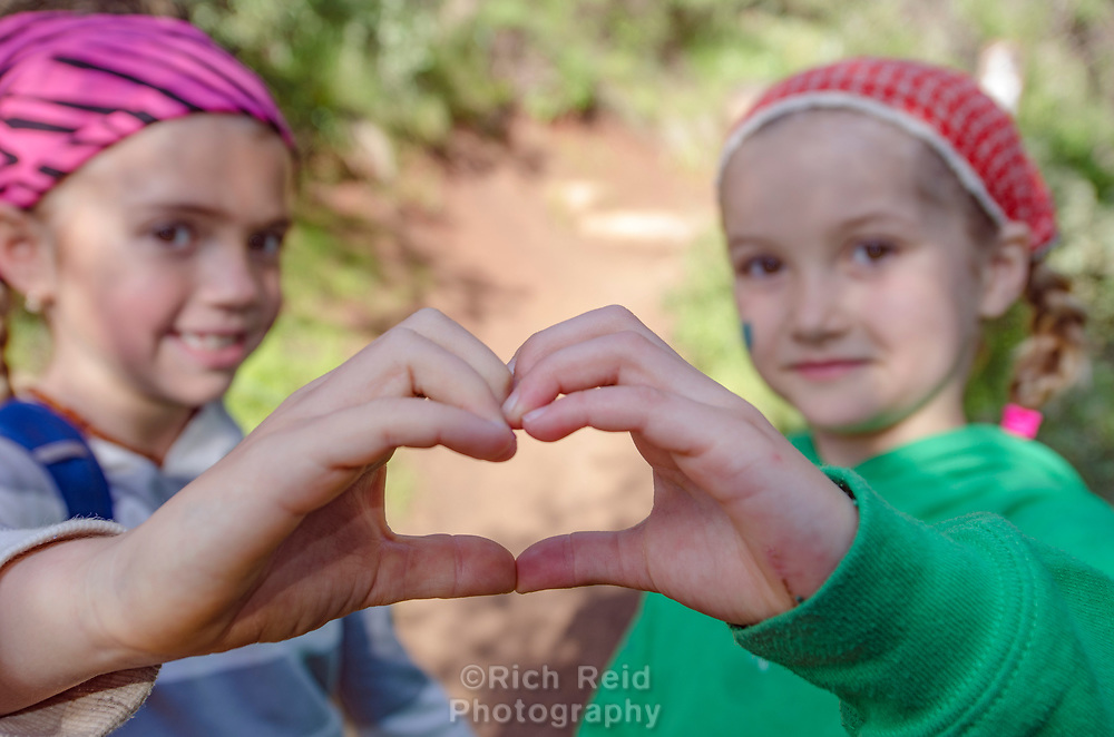 Two young girls showing a heart symbol with their hands on Pratt Trail in Los Padres National Forest, Ojai, California.