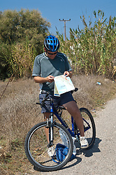 Cyclist reading A road map in Greece