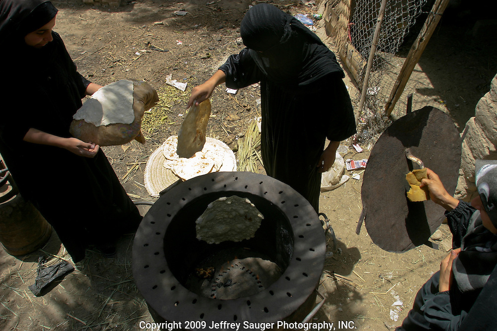 Women make traditional Iraqi flat bread during the Al-Kasid family's Istikbal, or homecoming, in their home village Suq ash Shuyukh, about 20 miles southeast of Nasiriyah, Iraq, Thursday, July 31, 2003...The women spend most of their time making dough, baking bread, milking cows, taking care of children, preparing food, etc. as the men gather out front of the compound. Women wear black as a sign of mourning for a close loved one that has died; some for a year and some forever after the death.