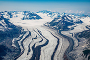 """Aerial view of Carroll Glacier, in Glacier Bay National Park, Alaska, USA. Flightseeing from Skagway or Haines is a spectacular way to see Glacier Bay. We were bedazzled by Mountain Flying Service's 1.3-hour West Arm tour from Skagway. Glacier Bay is honored by UNESCO as part of a huge Biosphere Reserve and World Heritage site shared between Canada and the United States. In 1750-80, Glacier Bay was totally covered by ice, which has since radically melted away. In 1794, Captain George Vancover found Icy Strait on the Gulf of Alaska choked with ice, and all but a 3-mile indentation of Glacier Bay was filled by a huge tongue of the Grand Pacific Glacier, 4000 feet deep and 20 miles wide. By 1879, naturalist John Muir reported that the ice had retreated 48 miles up the bay. In 1890, """"Glacier Bay"""" was named by Captain Beardslee of the U.S. Navy. Over the last 200 years, melting glaciers have exposed 65 miles of ocean. As of 2019, glaciers cover only 27% of the Park area. Since the mid 1900s, Alaska has warmed 3 degrees Fahrenheit and its winters have warmed nearly 6 degrees. Human-caused climate change induced by emissions of greenhouse gases continues to accelerate warming at an unprecedented rate. Climate change is having disproportionate effects in the Arctic, which is heating up twice as fast as the rest of Earth."""