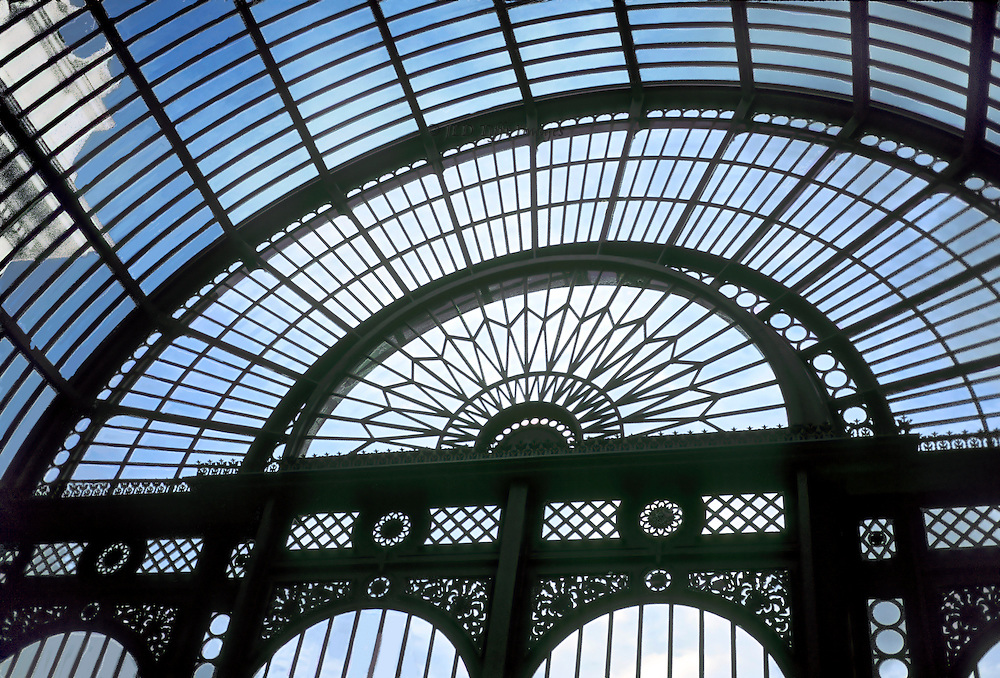 Covent Garden restored Flower Hall; interior view of the iron and glass arch over the original entrance.  A cornice of the Royal Opera House projects slightly into the image, giving a sense of scale.