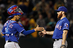OAKLAND, CA - JUNE 14:  Robinson Chirinos #61 of the Texas Rangers celebrates with Sam Dyson #47 after the game against the Oakland Athletics at the Oakland Coliseum on June 14, 2016 in Oakland, California. The Texas Rangers defeated the Oakland Athletics 10-6. (Photo by Jason O. Watson/Getty Images) *** Local Caption *** Robinson Chirinos; Sam Dyson