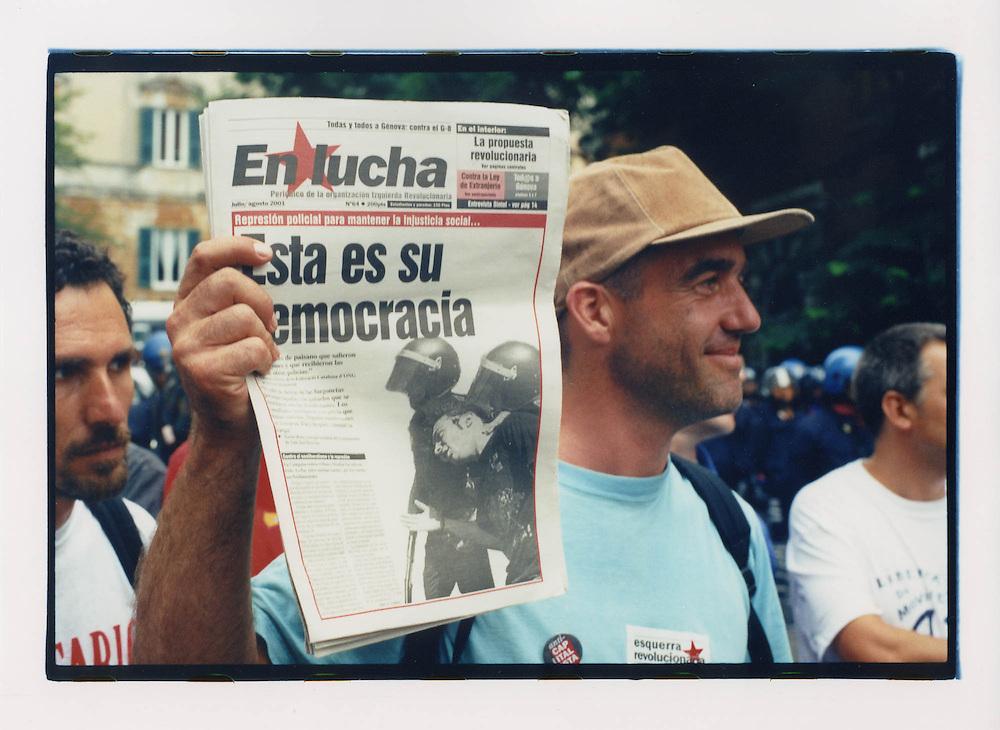Proteste contro il summit del G8, Genova luglio 2001. 19 luglio, corteo dei Migranti.  corteo dei Migranti. Un manifestante mostra un giornale che riporta recenti casi di repressione durante delle proteste in Spagna. Di lì a poche ore anche Genova diventerà il teatro di brutalità da parte delle forze dell'ordine, come in seguito denunciato, tra gli altri, da Amnesty International.