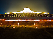"22 FEBRUARY 2016 - KHLONG LUANG, PATHUM THANI, THAILAND: Buddhist monks participate in the candle light procession around the chedi during the Makha Bucha Day service at Wat Phra Dhammakaya.  Makha Bucha Day is a public holiday in Cambodia, Laos, Myanmar and Thailand. Many people go to the temple to perform merit-making activities on Makha Bucha Day, which marks four important events in Buddhism: 1,250 disciples came to see the Buddha without being summoned, all of them were Arhantas, Enlightened Ones, and all were ordained by the Buddha himself. The Buddha gave those Arhantas the principles of Buddhism, called ""The ovadhapatimokha"". Those principles are:  1) To cease from all evil, 2) To do what is good, 3) To cleanse one's mind. The Buddha delivered an important sermon on that day which laid down the principles of the Buddhist teachings. In Thailand, this teaching has been dubbed the ""Heart of Buddhism."" Wat Phra Dhammakaya is the center of the Dhammakaya Movement, a Buddhist sect founded in the 1970s and led by Phra Dhammachayo. The temple is famous for the design of its chedi, which some have likened to a flying saucer or UFO.                PHOTO BY JACK KURTZ"