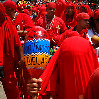 DANCING DEVILS OF YARE / LOS DIABLOS DE YARE<br /> Photography by Aaron Sosa<br /> Yare, Miranda State - Venezuela 2009.<br /> (Copyright © Aaron Sosa)<br /> <br /> The Dancing Devils of Yare is a religious festival held in the town of San Francisco de Yare in Miranda State, Venezuela.<br /> <br /> Every Corpus Christi, or 60 days after Easter, men from Yare dress in red robes, capes and masks of grotesque demons and dance in the streets to the rhythm of drumbeats and maracas. They adorn...<br /> more »<br /> DANCING DEVILS OF YARE / LOS DIABLOS DE YARE<br /> Photography by Aaron Sosa<br /> Yare, Mirana State - Venezuela 2009.<br /> (Copyright © Aaron Sosa)<br /> <br /> The Dancing Devils of Yare is a religious festival held in the town of San Francisco de Yare in Miranda State, Venezuela.<br /> <br /> Every Corpus Christi, or 60 days after Easter, men from Yare dress in red robes, capes and masks of grotesque demons and dance in the streets to the rhythm of drumbeats and maracas. They adorn their costumes with scapulars, rosaries, crosses and other religious objects.<br /> <br /> After dancing the devils congregate at the historical San Francisco Catholic church and kneel in silence before being blessed by a priest. The kneeling symbolizes respect and their religious promise to end their evil ways. After being blessed, dancing and music continue as the devils go in a large procession to visit the homes of the deceased throughout their town. The celebration lasts until the end of the afternoon, when church bells are sounded and brotherhood spreads, signifying the triumph of good over evil for one more year.<br /> <br /> The festival's origins date back to the eighteenth century, and being allowed to participate is considered a tremendous honor. The fraternity of men associated with the festival is celebrated as the oldest brotherhood still practicing its traditions, on the entire American continent. Their masks differentiate their place in the fraternity's hierarchy