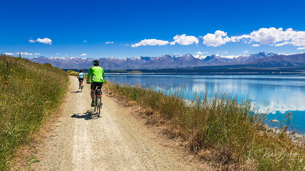 Cyclists riding along the shore of Lake Pukaki under the Southern Alps, Canterbury, South Island, New Zealand