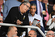 "Former Brighton manager Chris Hughton chats to Talksport presenter Ian ""The Moose"" Abrahams during the Pre-Season Friendly match between Northampton Town and Sheffield United at the PTS Academy Stadium, Northampton, England on 20 July 2019."