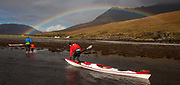 Family come ashore in sea kayaks, rainbow over Glen Brittle, The Cuillins, The Highlands, Scotland
