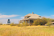 Old house and grain elevator in ghost town<br /> Fusiller<br /> Saskatchewan<br /> Canada