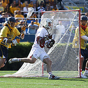 Denver Midfielder Erik Adamson (34), CENTER, attacks the net as Drexel Midfielder Mason Pynn (25), LEFT, defends in the second half of a NCAA Division I Men's Lacrosse Tournament game between the No. 5 seed Denver and No. 12 ranked Drexel Sunday, May. 18, 2014 at Delaware Stadium in Newark, DEL