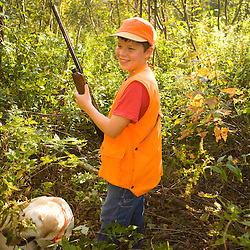 A boy hunting grouse and woodcock in a private forest in Jefferson, New Hampshire.