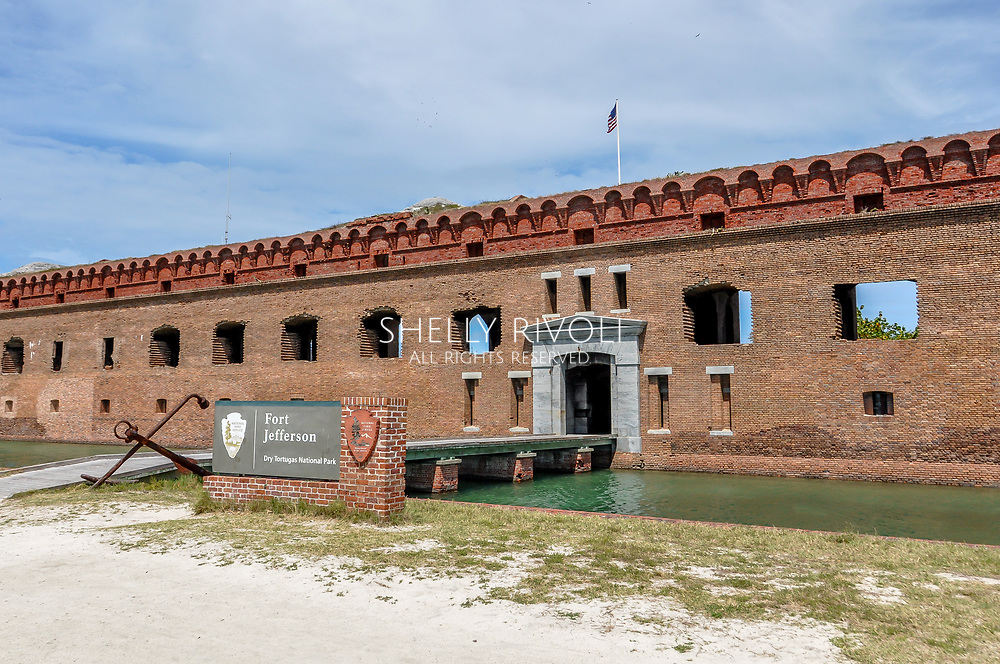 View of historic Fort Jefferson's entrance with moat crossing toward the brick building. No people are visible in this establishing shot.