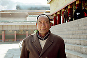 A tibetan pilgrim from the town of Maqu (Gansu pronvince), in the courtyard of the Main Assembly Hall of the Labrang monastery. He comes every year to see the ceremonies of Monlam Chenmo (the Great Prayer) and to visit his son, who became a high level monk of the Gelupka order after 15 years of buddhic texts studies. Xiahe, March 01 2007.