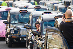 Whitehall, London, February 10th 2016. A cabbie poses for a colleague's camera as an estimated 8,000 cabbies hold a go-slow in protest against what they say is unfair competition from minicab and Uber drivers who do not have to undergo the rigorous training and checks required for the licenced taxi trade. ///FOR LICENCING CONTACT: paul@pauldaveycreative.co.uk TEL:+44 (0) 7966 016 296 or +44 (0) 20 8969 6875. ©2015 Paul R Davey. All rights reserved.