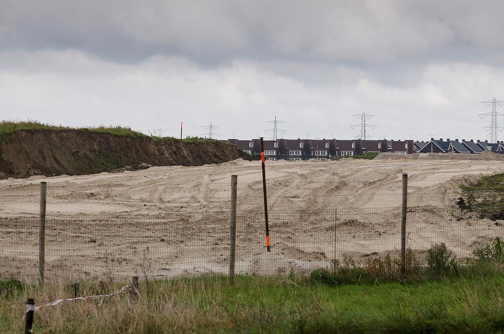 Nederland, Rosmalen, 20121013..Enorme afgravingen voor de omlegging van de Zuid-Willemsvaart. .Het kanaal dat door Den Bosch loopt wordt omgelegd langs de nieuwbouwwijk De Groote Wielen in Rosmalen. Zichtbaar achter de zandheuvels..Bij Rosmalen, gemeente Den Bosch wordt een nieuwe stad gebouwd, De Groote Wielen. In de nieuwe wijk worden 6500 woningen gebouwd. Het landschap verandert van een polderlandschap met agrarische bestemming in een stadslandschap..De rafelranden van een nieuwe stad...Netherlands, Rosmalen, 20121013..Huge excavation for the diversion of the South Willemsvaart..The canal that runs through Den Bosch is being build, diverted along the new district De Groote Wielen in Rosmalen. Visible in the background..Near Rosmalen a new town is being build,  De Groote Wielen. In the new district 6,500 homes are built. The landscape changes from a polder landscape with agricultural destination in a city landscape..The fringes of a new city.