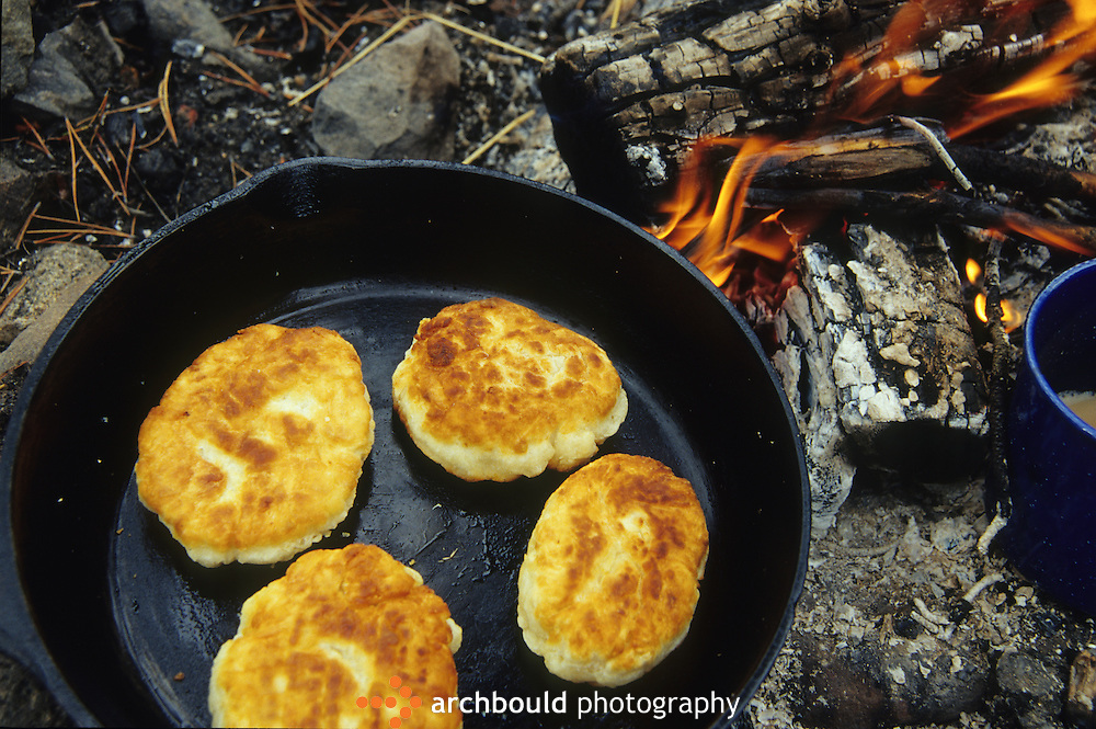Bannock cooking over an open campfire