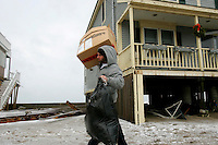 Justin LaCentra carries his belongings from his ocean-front apartment, at right, which was flooded out from a storm surge on Turner Road in Scituate, Massachusetts on December 27, 2010.  The surge was due to a blizzard  which caused coastal flooding and dumped over a foot and a half of snow in other parts of the state.   UPI/Matthew Healey