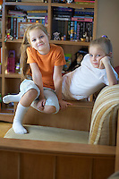 Two girls sit in playroom with shelving storage