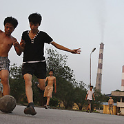 Boys play football outside the coal-powered electricty plant in Phai Lai, about 70 kilometers east of Hanoi, Vietnam, 14 September, 2007.