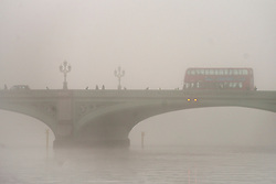 © Licensed to London News Pictures.11/12/2013. London, UK.People make their way across Westminster Bridge in fog this morning.Photo credit : Peter Kollanyi/LNP