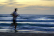 Motion blurred jogger on a beach at sunset