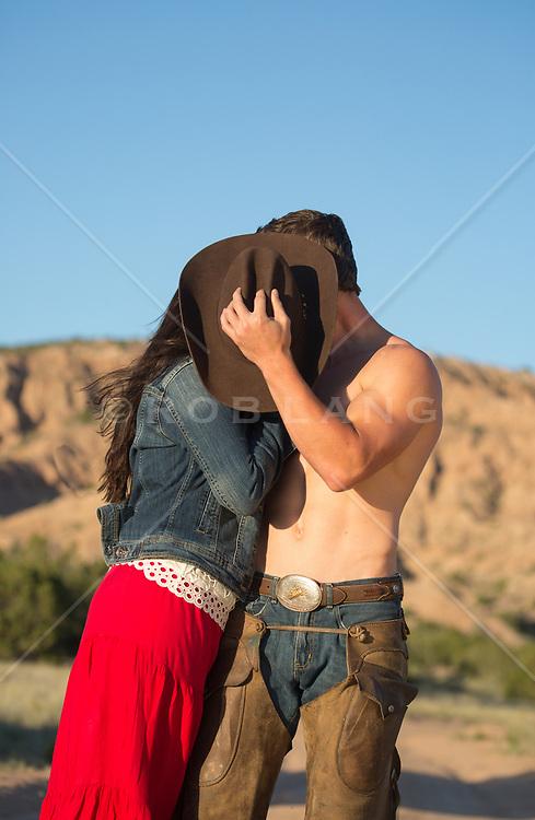cowboy and a girl kissing behind a cowboy hat