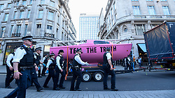 "© Licensed to London News Pictures. 19/04/2019. LONDON, UK.  Police officers form a cordon around the pink boat as it is removed from Oxford Circus during ""London: International Rebellion"", on day five of a protest organised by Extinction Rebellion.  Protesters are demanding that governments take action against climate change.  Police have issued a section 14 order requiring protesters to convene at Marble Arch only so that the protest can continue.  Photo credit: Stephen Chung/LNP"