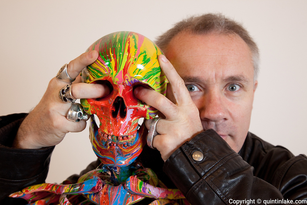 """Close-up Damien Hirst Portrait with fingers in eye sockets of skull of his artwork.""""St Elmo's Fire"""".2008.Household gloss on plastic skeleton.1700 x 425 x 435 mm.© Damien Hirst. All rights reserved, DACS 2010.Photographed in his Chalford Studio, near Stroud, Gloucestershire"""