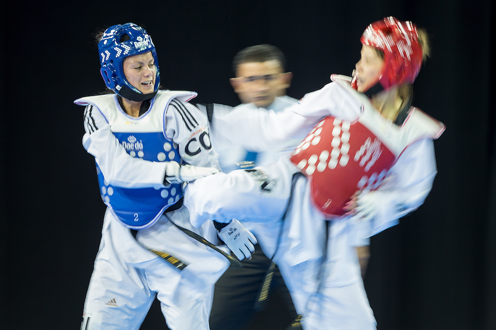 Doris Patino (L) of Colombia takes on Adriana Martinez of Venezuela  in their 1/8 round contest against Adriana Martinez in the -57kg weight class of Taekwondo at the 2015 Pan American Games in Toronto, Canada, July 20,  2015.  AFP PHOTO/GEOFF ROBINS