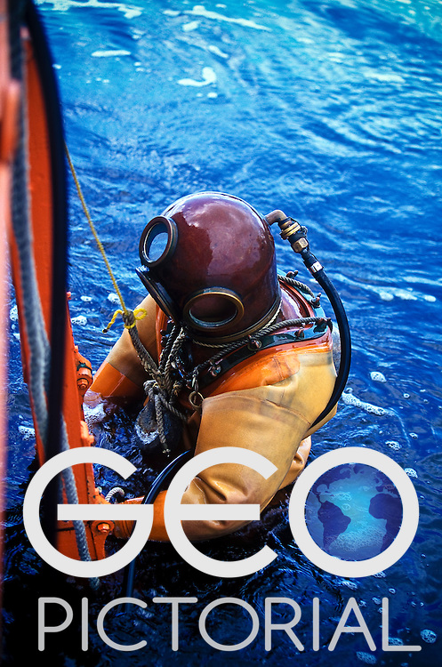 Tarpon Springs, Florida, USA; August 2003;.An exhibition sponge diver climbs up a ladder back on board the St Nicholas III traditional Greek sponge diving boat.